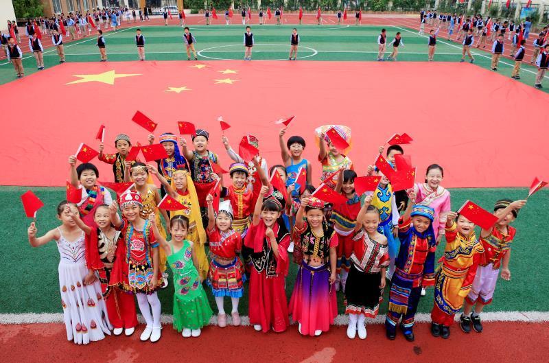 身穿民族服饰的小朋友一同祝福祖国。